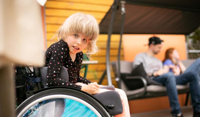 Ein Kind schaut seitlich aus dem Rolli raus. Im Hintergrund sitzen zwei Personen auf einer Hollywoodschaukel ©Helfende Hände/Fabian Helmich