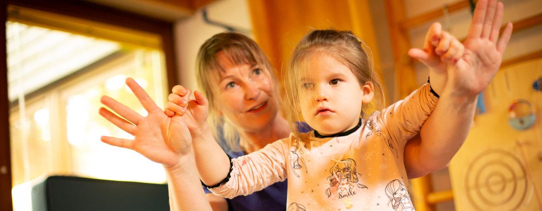 Ein Kind wird von einer Therapeutin an den Händen geführt ©Helfende Hände/Fabian Helmich