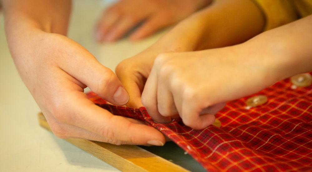 Die Hände eines Kindes machen einen Knopf zu. Die helfenden Hände einer Betreuerin unterstützen dabei ©Helfende Hände/Fabian Helmich