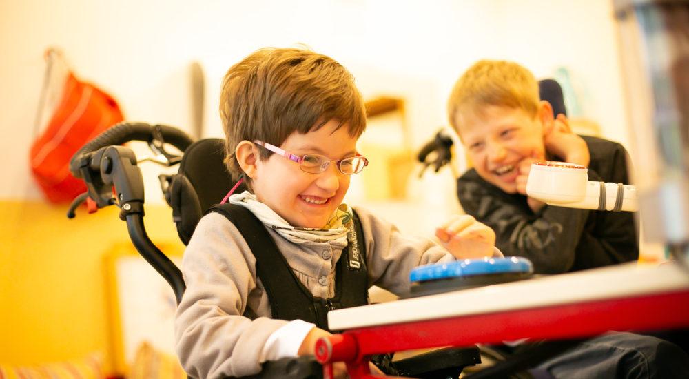 Eine Schüler im Rollstuhl sitzt am Tisch. Ein weiter Schüler lacht sie an. ©Helfende Hände/Fabian Helmich