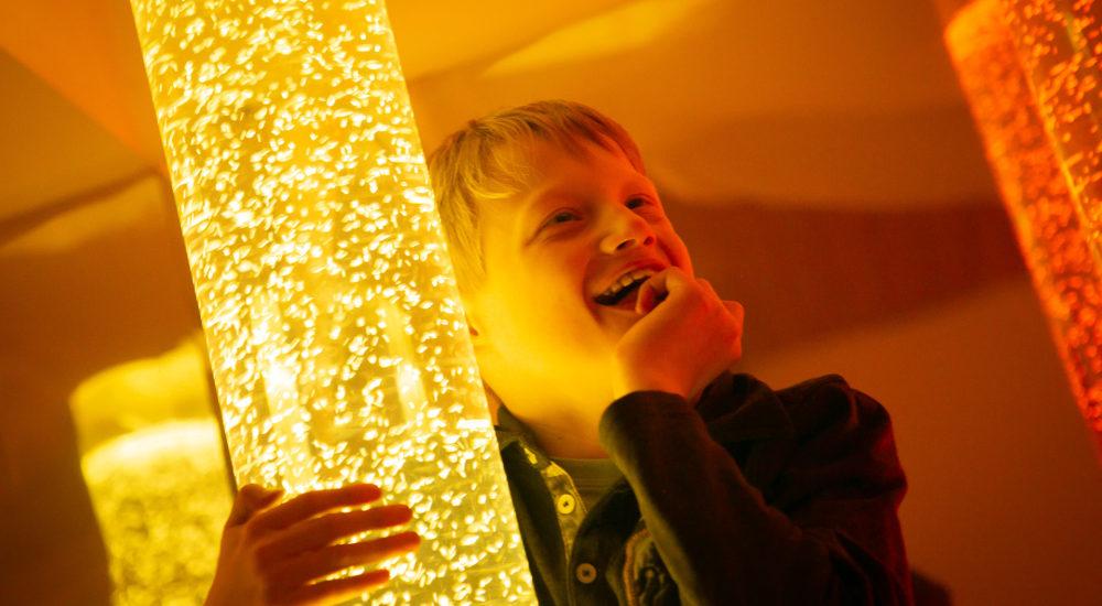 Ein Junge steht an einer Lichtsäule und freut sich ©Helfende Hände/Fabian Helmich