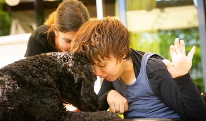 Eine Betreute stubst mir ihren Kopf einen Hund an ©Helfende Hände/Fabian Helmich