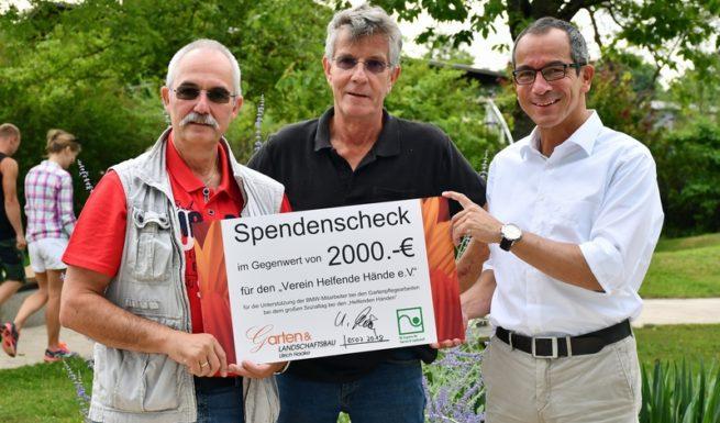 Drei Männer halten einen Scheck mit dem Aufdruck 2000 € in der Hand ©Helfende Hände