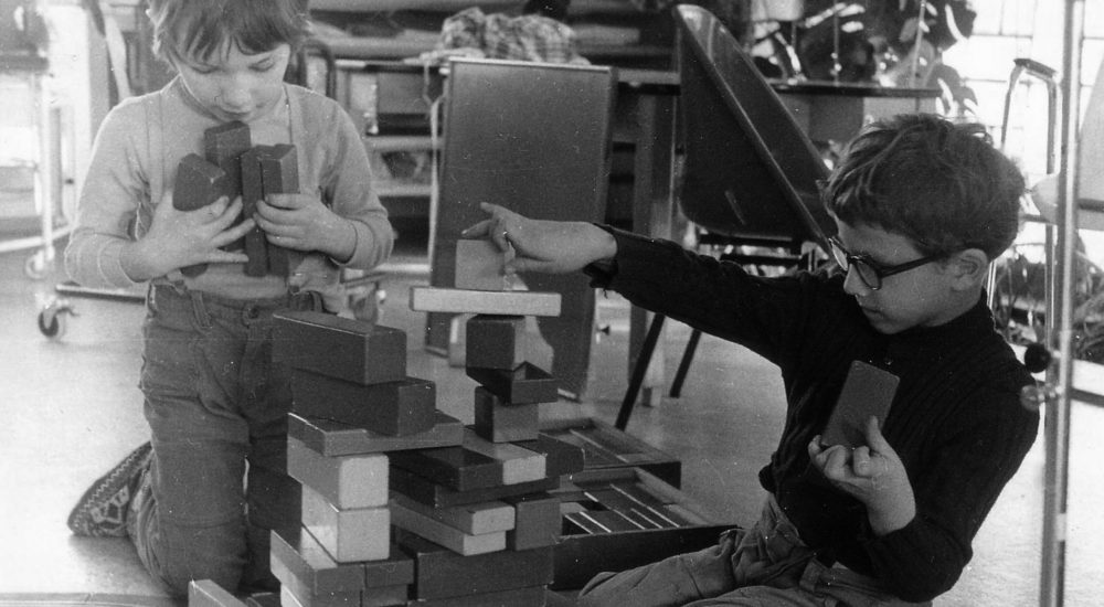 Ein historischen Schwarz-Weiß-Bild aus dem Jahr 1972 zeigt zwei spielende Kinder die einen Holzturm bauen ©Helfende Hände