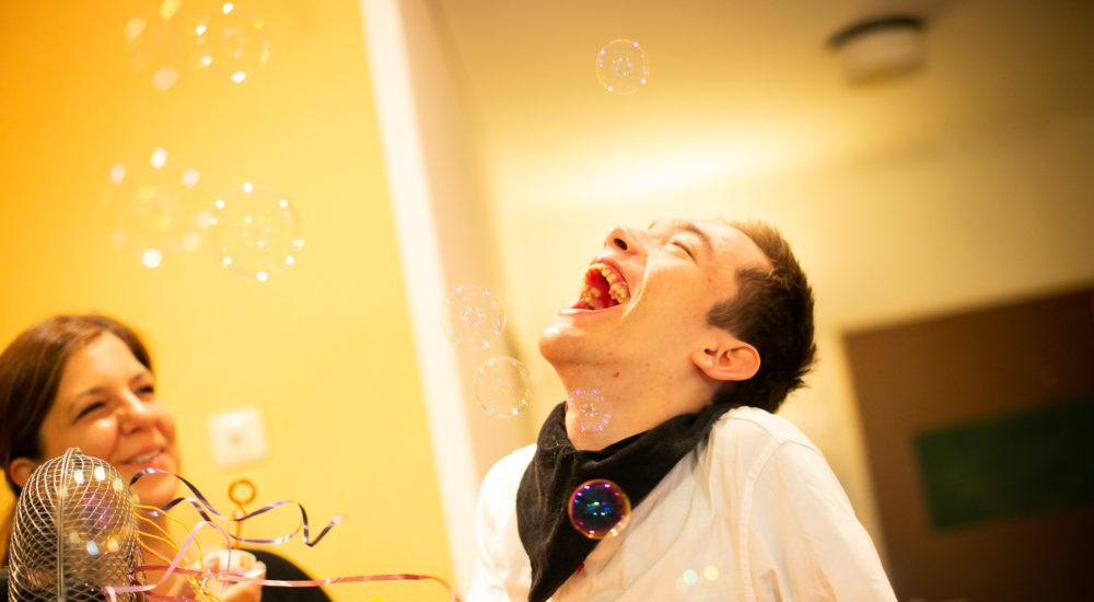 Ein Betreuter erfreut sich an zahlreichen herumwirbelnden Seifenblasen ©Helfende Hände/Fabian Helmich