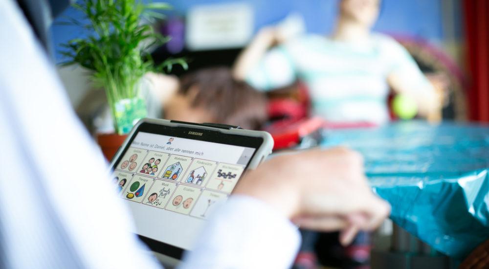 Ein Tabletcomputer mit Icons der Unterstützenden Kommunikation wird bedient ©Helfende Hände/Fabian Helmich