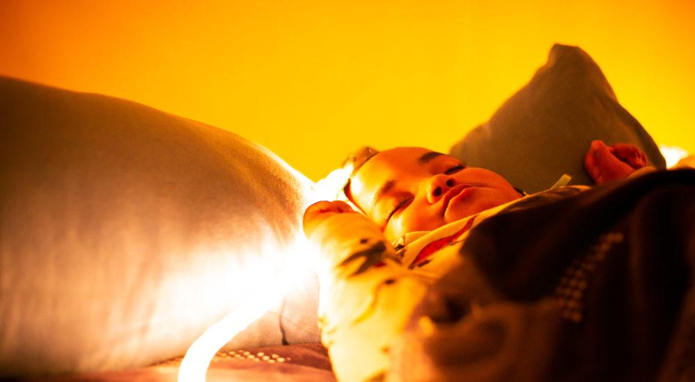 Ein Kind liegt auf einem Kissen und ruht sich aus. Die Augen sind geschlossen ©Helfende Hände/Fabian Helmich