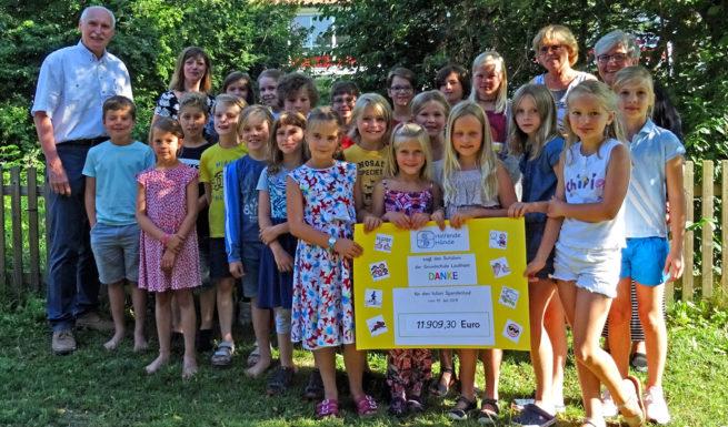 Schulleitung (Grundschule Lochham), Rektorin (Förderschule Helfende Hände), Elternbeirat (der Grundschule), und Vorstand (von Helfende Hände) samt zahlreichen Kindern halten einen Spendenscheck mit der Summe 11909,30 € in der Hand. ©Helfende Hände