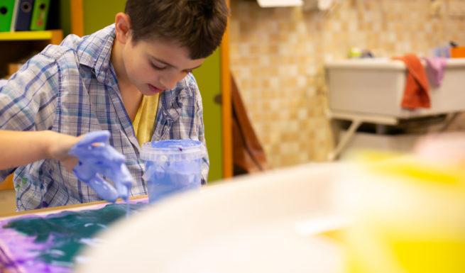 Ein kind das seine Hände in blaue Farbe getaucht hat, streicht damit über ein Blatt Papier ©Helfende Hände/Fabian Helmich