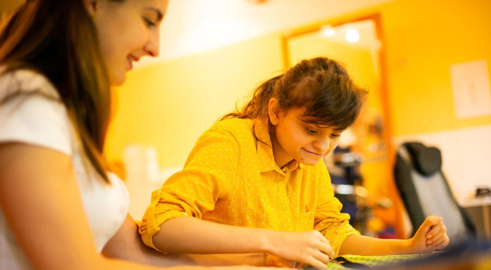 Eine Schülerin führt Hand- und Fingerübungen an einem Reißverschluß durch. Eine Betreuerin sitzt dabei. ©Helfende Hände/Fabian Helmich