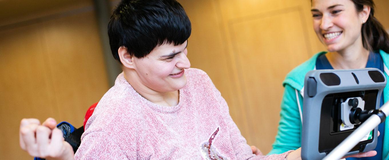 Eine Betreute arbeitet am Tablet und eine Logopädin lacht sie an ©Helfende Hände/Fabian Helmich