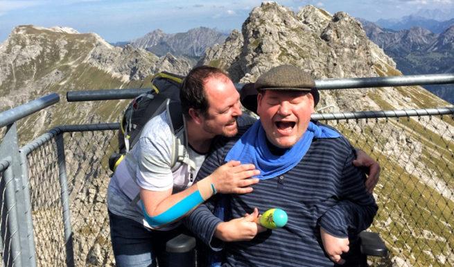 Ein Betreuter im Rollstuhl lacht. Ein Betreuer schaut ihn an. Beide befinden sich auf einem Berggipfel ©Helfende Hände