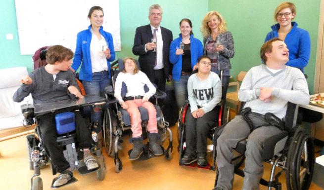 Vier Betreute, das Therapieteamm, Frau Zimpel vom Vorstand und Herr Karmann vom Lionsclub stoßen mit Sekt an. ©Helfende Hände
