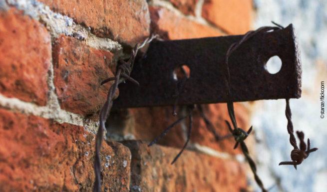 Ein Stück Stacheldraht an einer Mauer. Der Draht ist verrostet. ©stanze/flickr.com