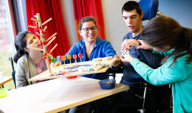 """Vier Menschen sitzen am Tisch und spielen das Spiel """"Cookiemonster"""" ©Helfende Hände/Fabian Helmich"""