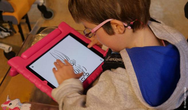 Aleka liebt ihr Tablet. Sie hält es in der Hand und spielt © Helmut Winkler