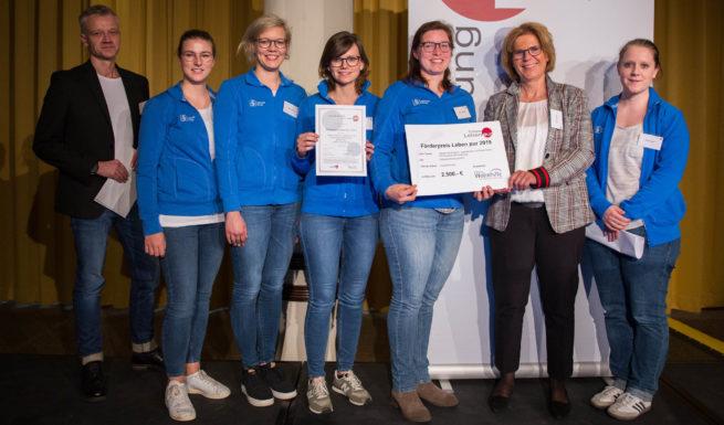 Fünf stahlende Personen vom Ergotherapie-Team stehen auf der Bühne und nehmen einen Scheck (2500 €) entgegen.