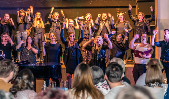 Viele Sängerinnen und Sänger stehen auf eine Bühe und singen begeisternd die Hände in die Luft gestreckt ©Oliver Heuft