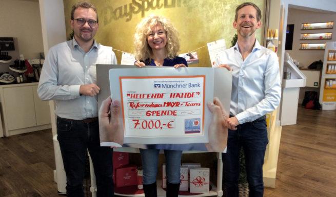 Wolfgang J. Schreiter, Nariman Zimpel und Michael Mayr halten einen Scheck in Höhe von 7000 € in der Hand