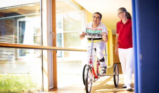 Betreuter von Helfende Hände in München mit Therapeutin beim Dreiradfahren ©Helfende Hände/Fabian Helmich