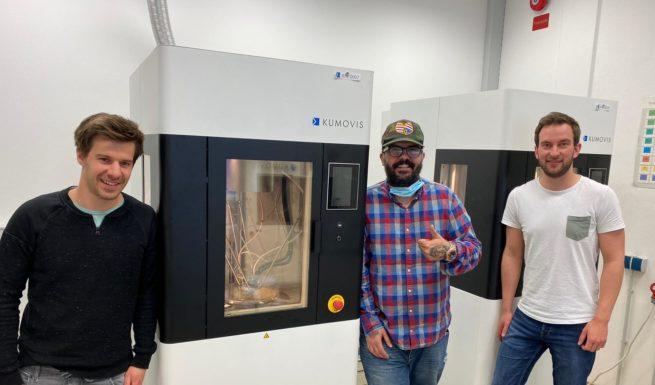 """Helfende-Hände-Mitarbeiter Slaven Ivankovic mit Angestellten von Kumovis beim 3D-Druck der """"Ohren-Dinger""""."""