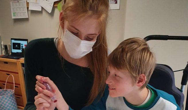 """Kevin Mittermeier und Annett Benker vom Förderzentrum von Helfende Hände malen das Plakat """"Wir sind es wert""""."""