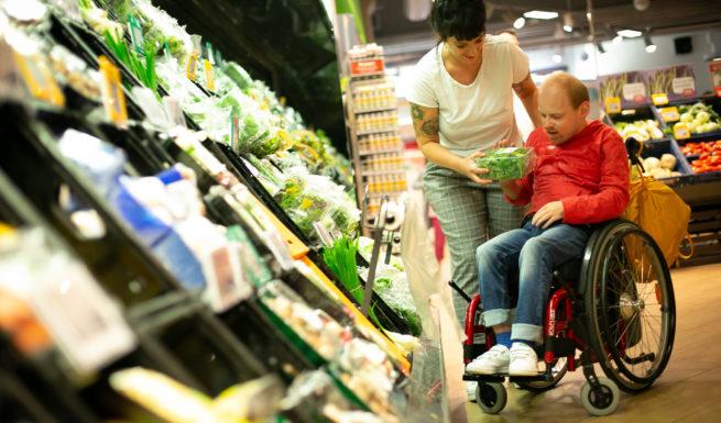 Bewohner und Mitarbeiterin von Helfende Hände beim Lebensmittel einkaufen